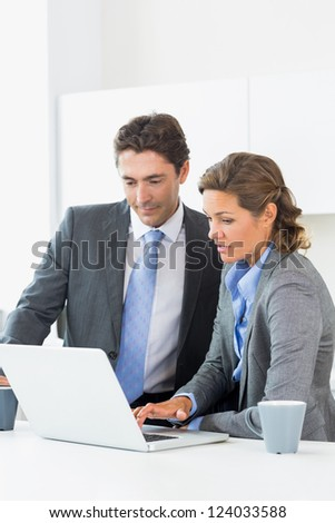 Couple looking at the laptop in kitchen before work - stock photo