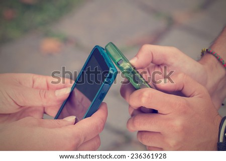 Couple looking at their smart-phones in the park.