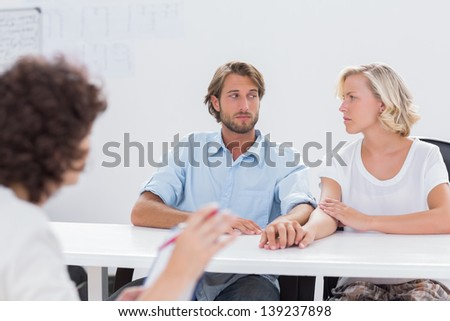 Couple looking doubtful during therapy session as therapist is gesturing at them