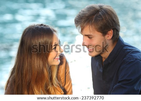 Couple looking each other in love on vacations with the sea in the background - stock photo