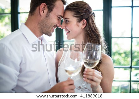 Couple looking face to face and toasting wine glasses in a restaurant - stock photo