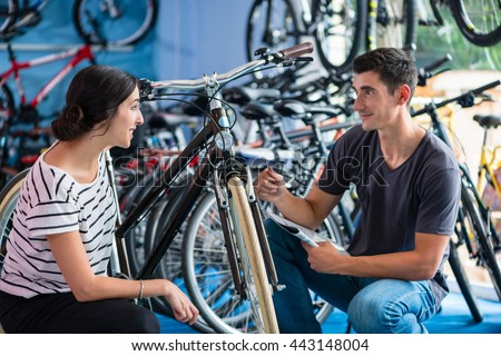 Couple looking for bicycle in bike shop - stock photo
