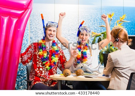 Couple looking forward to beach vacation wearing snorkeling equipment in travel agency - stock photo