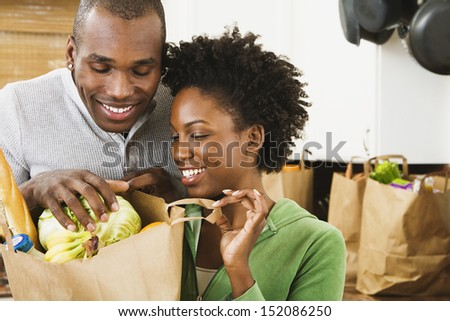 Couple looking in grocery bag - stock photo