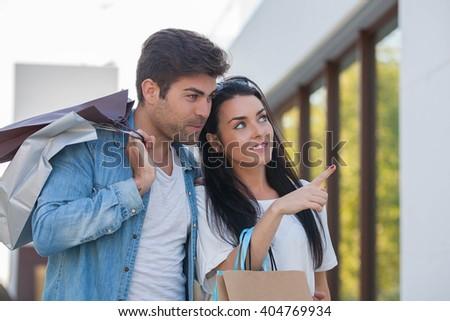 COUPLE LOOKING IN SHOP WINDOW - stock photo