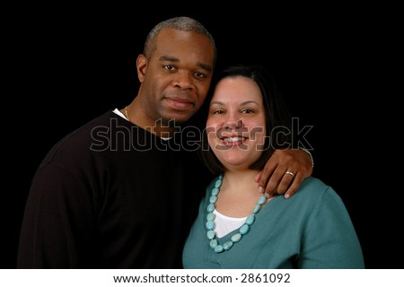 Couple looking into camera over a black background.