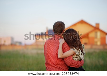 couple looking on house - stock photo