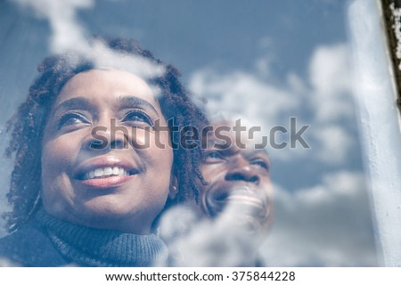Couple looking out of a window - stock photo
