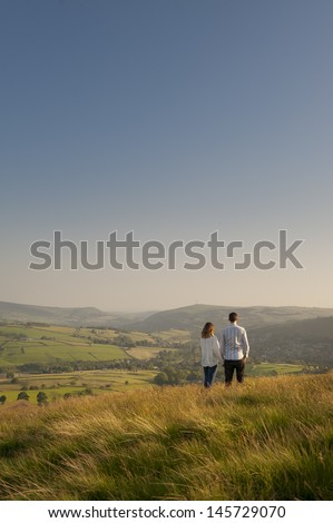 couple looking over a valley to hills beyond - stock photo
