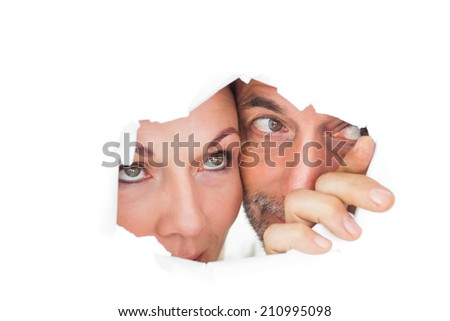 Couple looking through torn paper on white background - stock photo