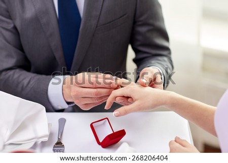 couple, love, engagement and holiday concept - close up of man putting ring to his fiance finger at restaurant - stock photo