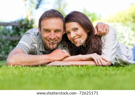 Couple lying down in the garden - stock photo