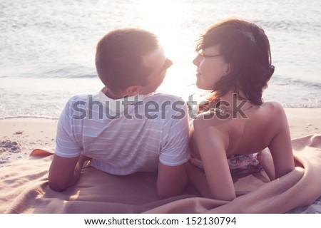 Couple lying down on sand near from the sea or ocean beach - stock photo