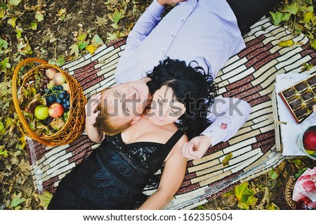 Couple lying in a park while having picnic - stock photo