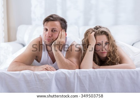 Couple lying in bed is not talking after argument - stock photo