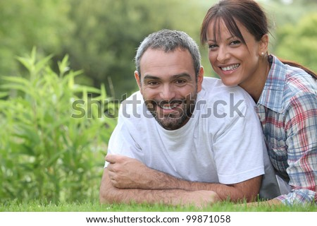 Couple lying in grass - stock photo