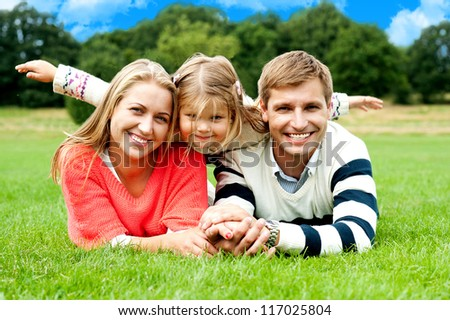 Couple lying in park with their daughter on top. Daughter stretching her hands sideways - stock photo