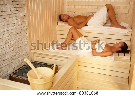 Couple lying in sauna wearing towel, relaxing with eyes closed.? - stock photo