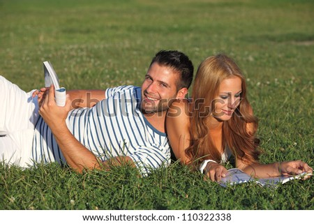 Couple lying in the park and reading - stock photo