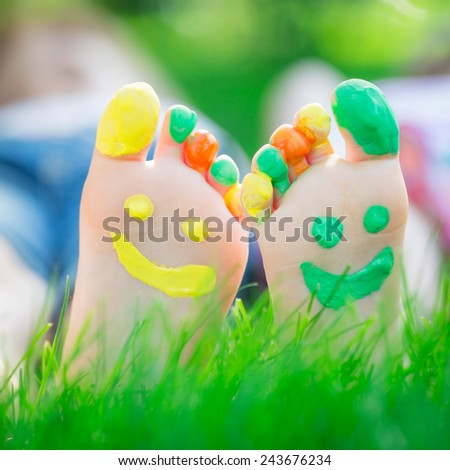 Couple lying on green grass. Children having fun outdoors in spring park - stock photo