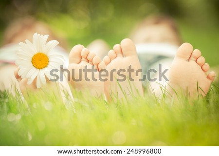 Couple lying on green grass. People having fun outdoors in spring park - stock photo