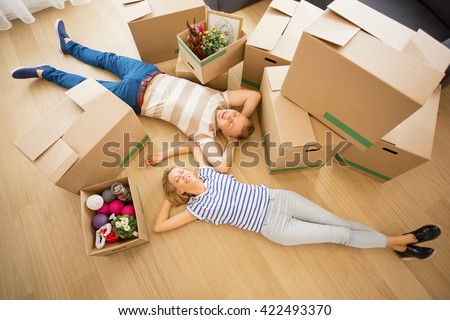 Couple lying on the floor in their new apartment - stock photo