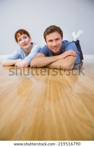 Couple lying on the floor looking at the camera