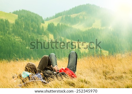 Couple lying on the hills with beautiful mountains in the foreground - stock photo