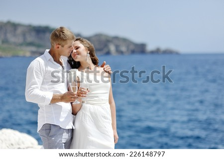 couple making a toast by the sea after their wedding in Naples, Italy