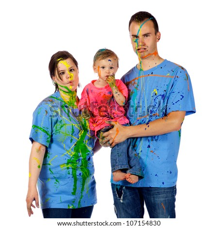 Couple making faces as they holding their toddler after having a paint fight together. - stock photo