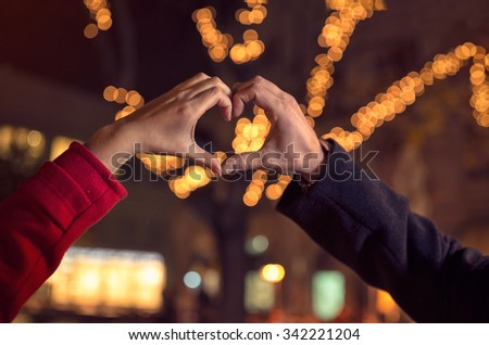 couple making heart shape with hands over the Christmas illumination - stock photo