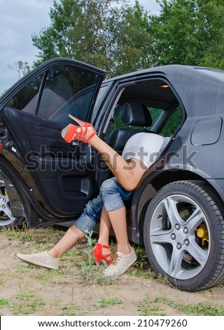 Couple making love on the car's backseat. - stock photo