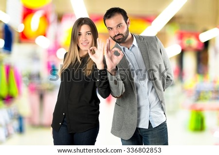 Couple making Ok sign over unfocused background