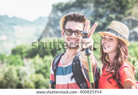 Couple making trekking on the hills. Smiling at camera. Concept about leisure and relationships - stock photo