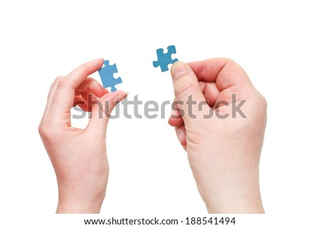 couple male and female hands with blue puzzle pieces isolated on white background - stock photo