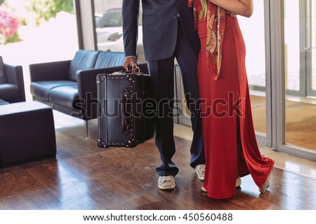Couple man and woman at the reception desk holding leather vintage style suitcase trunk, interior background - stock photo