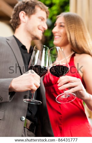 Couple, man and woman, at wine tasting in a restaurant, each with glass of red wine in hand - stock photo