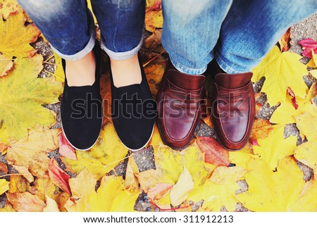 Couple Man and Woman Feet in Love Romantic Outdoor with Autumn season nature on background Fashion trendy style. Top view on shoes. Photo toned style instagram filters