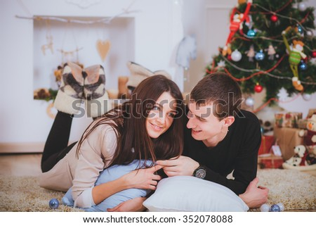 couple man and woman hugging, lie near the Christmas tree