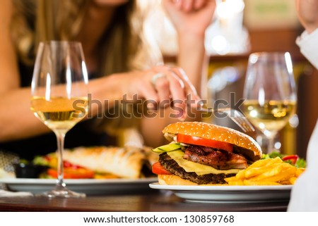 Couple - man and woman - in a fine dining restaurant they eat fast food, burger and fries, closeup - stock photo