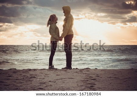 Couple Man and Woman in Love standing on Beach seaside holding hand in hand with Beautiful Sunset sky scenery People Romantic relationship and Friendship concept trendy moody colors - stock photo