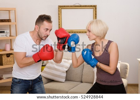 Couple man and woman in red and blue boxing gloves having battle at home. Man and woman demonstrating about positive or negative lifestyle.