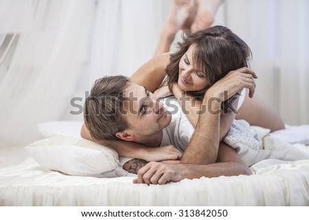 Couple man and woman lay cuddling on the bed at home. Love, family, relationships - stock photo