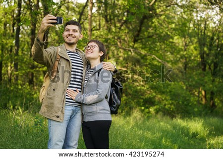 couple man and woman with backpacks in the forest in a still image to your phone in social networks.