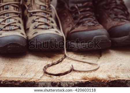 Couple man and women hiking boots in love outdoor. Lifestyle travel relationship. Summer vacations. Woman and man, family trekking shoes. Laces in heart shape. Love to travel concept. Outdoor items. - stock photo