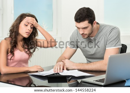 Couple, Man angry and upset after looking at credit card statement. - stock photo