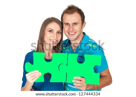 Couple matching to each other holding puzzle pieces isolated on white