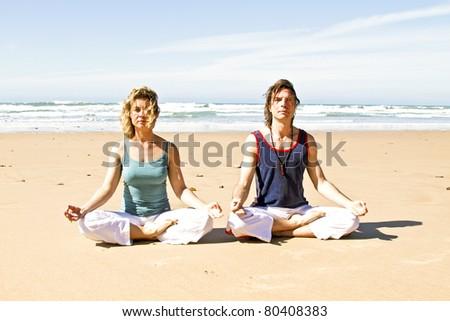 Couple meditating at the beach - stock photo