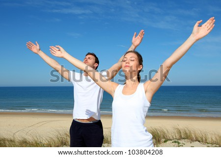 Couple meditating at the beach with arms up - stock photo