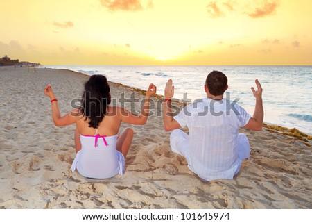 Couple meditating together on the Caribbean Sea at sunrise - stock photo